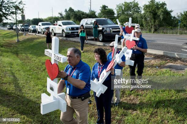People carry crosses made by Greg Zanis for the victims of the Santa Fe High School to the high school on May 21 2018 in Santa Fe Texas