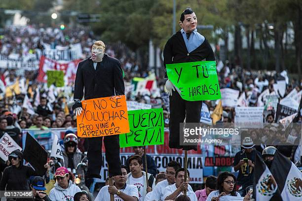 People carry effigies of Mexican President Enrique Pena Nieto and US Presidentelect Donald Trump during a protest against the rise in gasoline prices...