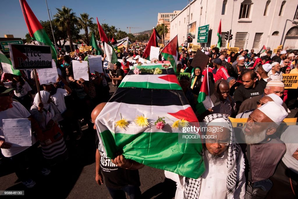 People carry fake coffins as thousands march through Cape Town city centre on May 15, 2018 to mark Nakba Day, an annual event which commemorates the displacement of Palestinians in 1948, and to protest against the killing, the day before, of 59 Palestinians in clashes and protests, on the same day as the United States formally moved its embassy in Israel to Jerusalem from Tel Aviv in defiance of international outrage.