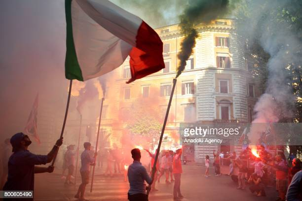 People carry flags and flares during a protest against the law on Jus Soli which would give birthright citizenships to children born to refugees...