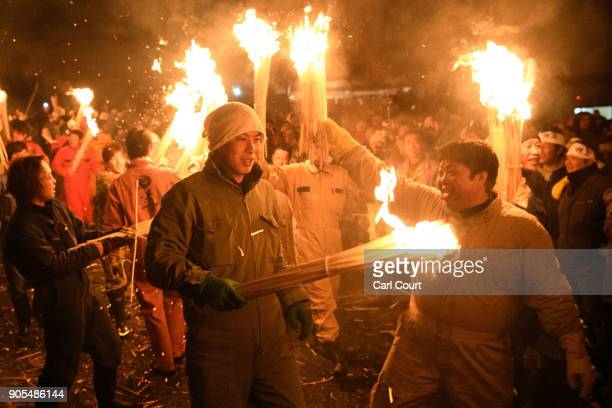 People carry flaming sticks as they try to set fire to a wooden shrine that is protected by men from Nozawaonsen village during the Nozawaonsen...