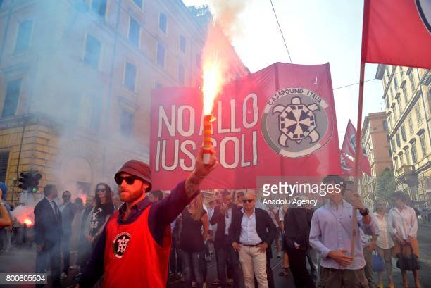 People carry flares and flags during a protest against the law on Jus Soli which would give birthright citizenships to children born to refugees...