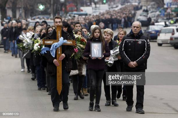 People carry flowers a wooden cross and a portrait of assassinated prominent Kosovo Serb politician Oliver Ivanovic as they accompany the coffin of...