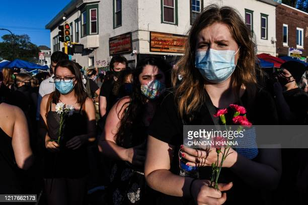 People carry flowers as they pay visit at the makeshift memorial in honour of George Floyd on June 4 2020 in Minneapolis Minnesota On May 25 Floyd a...