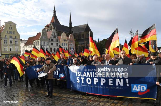 People carry German flags and a banner which reads Stop Islamization during a march organised by the rightwing populist AfD in Rostock northeastern...