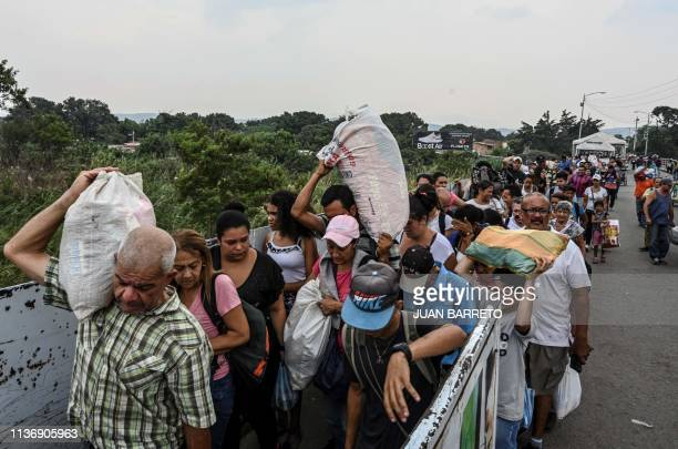 People carry goods as they cross the international border bridge Simon Bolivar from the Colombian city of Cucuta back to San Antonio del Tachira in...