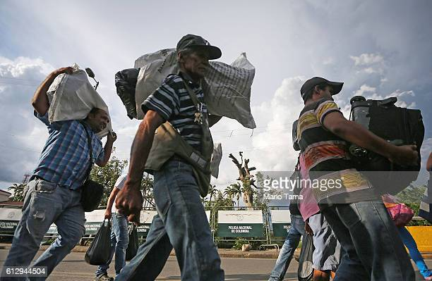 People carry goods purchased in Colombia across the international border bridge back to Venezuela on October 4 2016 in Cucuta Colombia The dire...