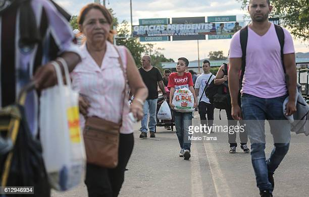People carry goods purchased in Colombia across the international border bridge back to Venezuela on October 5 2016 in Cucuta Colombia The dire...