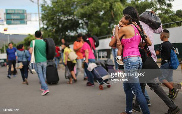 People carry goods purchased in Colombia on their way to cross the international border bridge back to Venezuela on October 4 2016 in Cucuta Colombia...