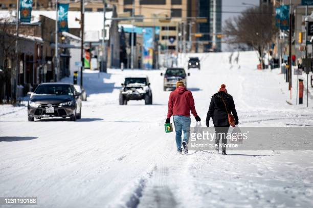 People carry groceries from a local gas station on February 15, 2021 in Austin, Texas. Winter storm Uri has brought historic cold weather to Texas,...