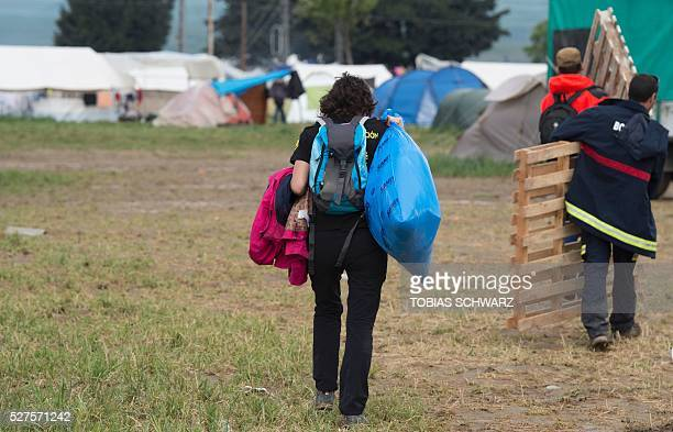 People carry items in a makeshift camp for migrants and refugees at the the GreekMacedonian border near the village of Idomeni on May 3 2016 The EU...