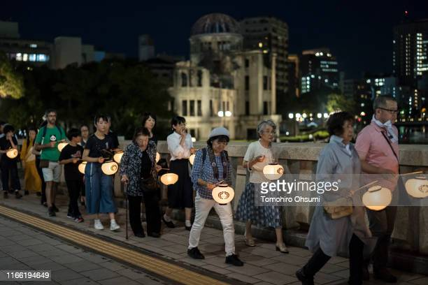 People carry lanterns past the Atomic Bomb Dome at the Hiroshima Peace Memorial Park on August 5 2019 in Hiroshima Japan Japan is preparing to mark...
