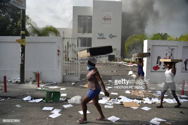 People carry loot from a shop in the commune of Petion Ville during protest against the increase in fuel prices July 7 2018 in PortauPrince Haiti's...
