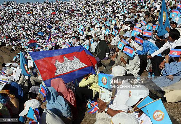 People carry national flags during a ceremony marking the 30th anniversary of the fall of the Khmer Rouge regime at the National Stadium in Phnom...