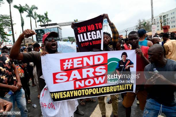 People carry placards in continuation of ongoing demonstrations to call for the scrapping of the controversial police unit at Ikeja, on October 9,...