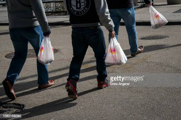 People carry plastic bags during the lunch hour in Lower Manhattan January 15 2019 in New York City New York Governor Andrew Cuomo is planning to...