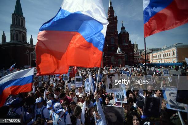 People carry portraits of World War II soldiers as they take part in the Immortal Regiment march during the Victory Day celebrations in Moscow on May...