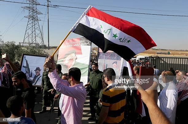 People carry posters of Saddam Hussein and Tariq Aziz during the funeral of Tariq Aziz in Amman Jordan on June 13 2015 Tariq Aziz former deputy prime...