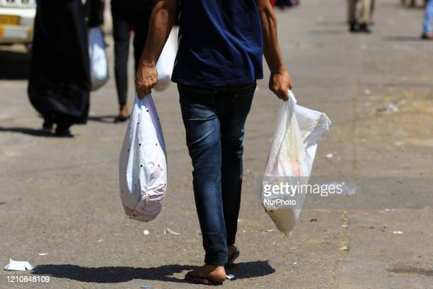 People carry rashan ' Essential foods' during the nationwide Lockdown imposed in the wake of the deadly novel coronavirus pandemic in Jaipur,...