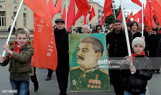 People carry red flags and a portrait of Soviet dictator Joseph Stalin during a march on December 21 in his native town of Gori west of Tbilisi to...