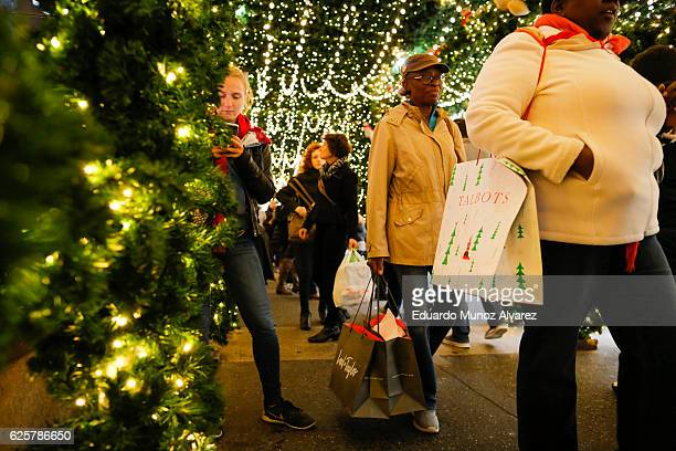 People carry retail shopping bags through holiday decorations during Black Friday events on November 25 2016 in New York City The day after...
