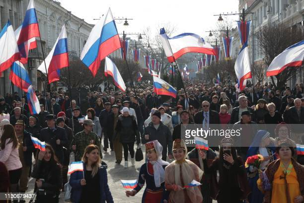 People carry Russian flags during celebrations of the fifth anniversary of Russia's annexation of Crimea in Simferopol on March 15, 2019.