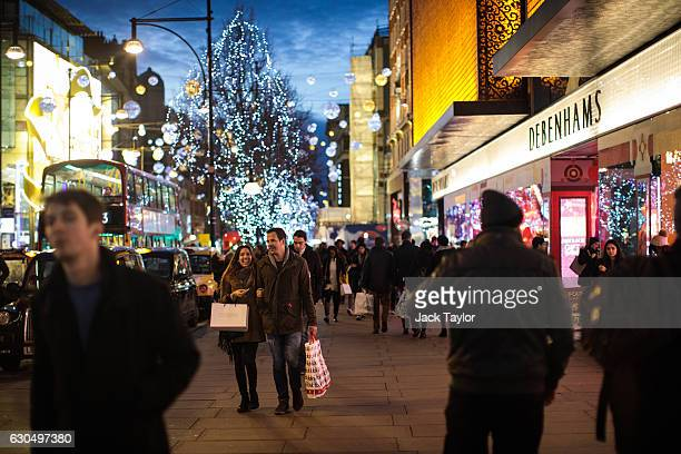 People carry shopping bags along Oxford Street on December 24 2016 in London England Christmas shoppers hunt for last minute presents in central...