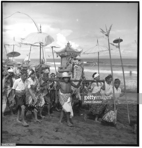 People carry shrines to the seaside to give the Gods who occupy them an airing and a bath as part of a Tembrah ceremony in Bali