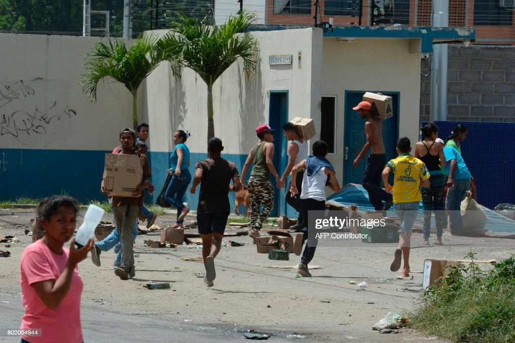People carry stolen merchandise after looting a supermarket in Maracay, Aragua state, Venezuela on June 27, 2017. / AFP PHOTO / Federico Parra