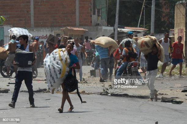 People carry stolen merchandise during lootings in Maracay Aragua State Venezuela on June 27 2017 A political and economic crisis in the oilproducing...