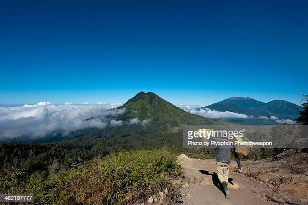 people carry sulphur blocks at kawa ijen indonesia - caldera stock pictures, royalty-free photos & images