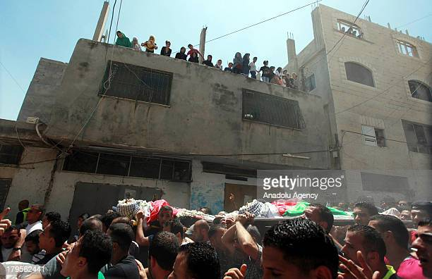People carry the bodies at the funeral of three Palestinians on August 262013 at the Qalandia Refugee Camp near Ramallah Palestine The 3 Palestinians...