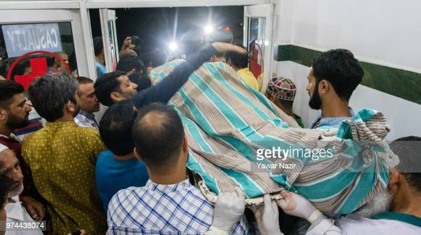 People carry the body of Syed Shujaat Bukhari the editor of Rising Kashmir daily newspaper who was killed by unidentified gunmen outside his office...