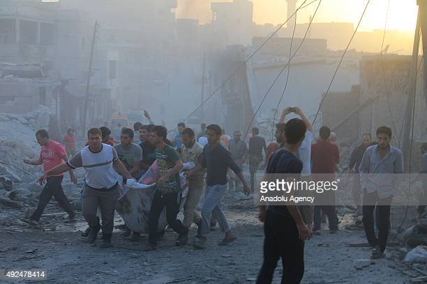 People carry the casualties at the attack site after Russian war crafts hit the Syrian opposition controlled town Daret Ezza in Aleppo Syria on...