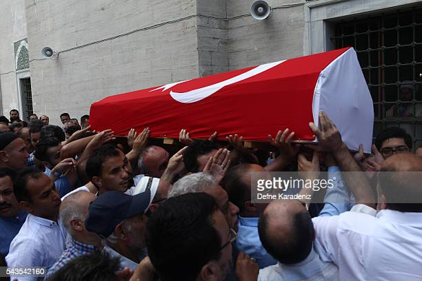 People carry the coffin drapped with the Turkish flag of taxi driver Mustafa Biyikli who lost his life in the following yesterday's suicide bomb...