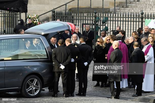People carry the coffin in the hearse outside the La Madeleine Church at the end of the funeral ceremony in tribute to late French singer Johnny...
