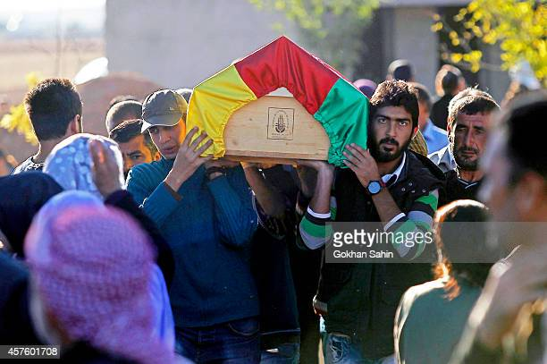 People carry the coffin of a Kurdish People's Protection Unit fighter who was killed during clashes against Islamic State in Kobani, Syria, during a...