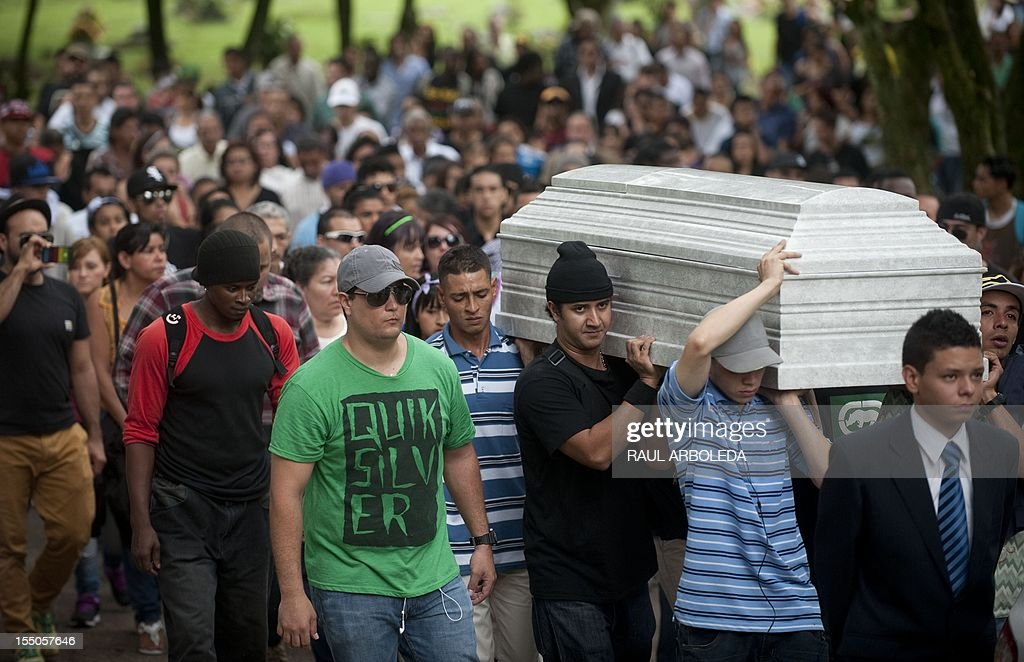 People carry the coffin of rapper Elider Varela, aka 'El Duke' during his funeral at Campos de Paz cemetery in Medellin, Antioquia deparment, Colombia on October 31, 2012. El Duque was killed by gunmen at the commune 13 shantytown , where he had become a peace leader through the lyrics of his songs. Varela became the seventh hip hop singer murdered in this city since 2010. AFP PHOTO / Raul ARBOLEDA