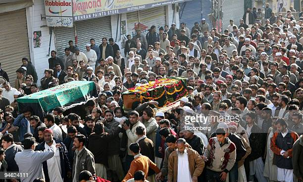 People carry the coffins of supporters killed in the bomb blast yesterday which also killed former Pakistani Prime Minister Benazir Bhutto through...