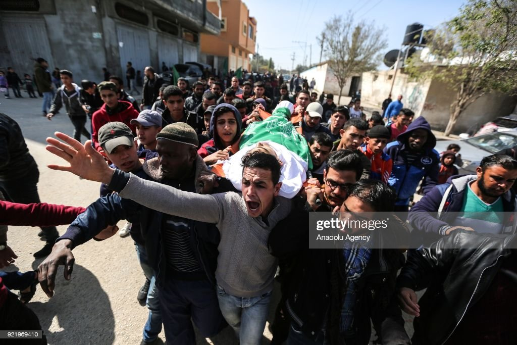 People carry the dead body of 19-years-old Ahmed Ebu Helou, who was killed by Israeli forces on protest against US decision to recognize Jerusalem as Israel's capital, during a funeral ceremony at Al-Beric refugee camp in Gaza City, Gaza on February 21, 2018.