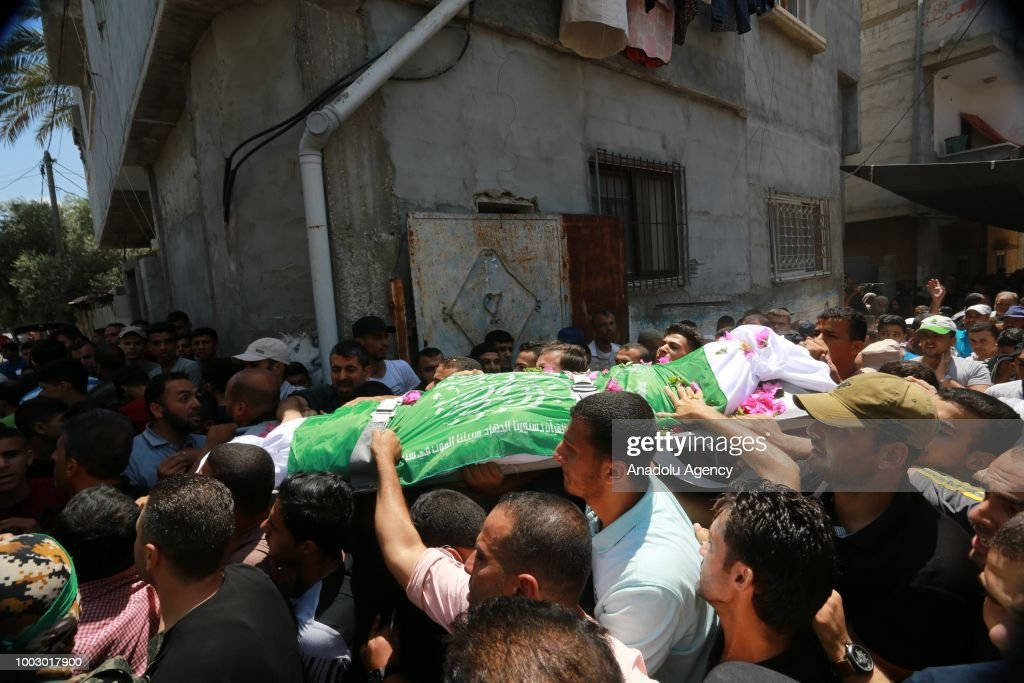 People carry the dead body of Mahmood Khaista (23), a member of the Izz ad-Din al-Qassam Brigades killed after Israeli attacks over Gaza Strip on July 20, during his funeral ceremony in Rafah, Gaza on July 21, 2018.