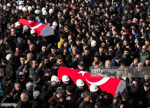 People carry the flagdraped coffins of police officers killed in yesterday's blast on December 11 2016 in Istanbul Turkey According to Interior...