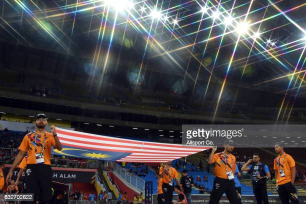 People carry the Malaysian flag into the field during the prematch ceremony during the Men Football Group A competition between Singapore and...