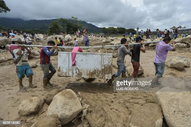 TOPSHOT People carry their belongings amidst the rubble left by mudslides following heavy rains in Mocoa Putumayo department southern Colombia on...