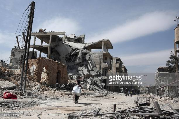 People carry their belongings as they flee their homes in the town of Hamouria in Syria's eastern Ghouta region on March 15, 2018. On February 18,...