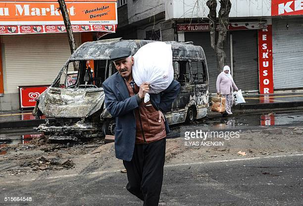 People carry their belongings as they leave their houses during clashes in central Diyarbakir on March 15 2016 / AFP / ILYAS AKENGIN