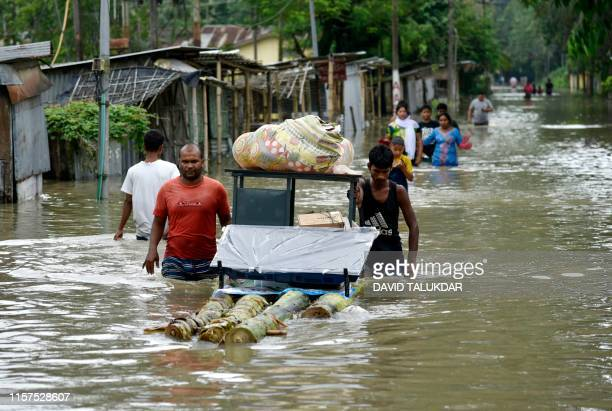 People carry their belongings as they walk through flood waters after the Pahumara river overflowed in Pathsala in Barpeta district of Assam on July...