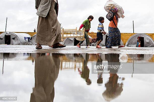 People carry their belongings in a refugee camp after crossing from Syria into Turkey in Suruc September 28 2014 south of Sanliurfa Turkey Islamic...