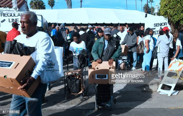 People carry their boxed Thanksgiving meals at the 35th annual EJ Jackson Foundation Turkey Grocery Giveaway after waiting in line for hours for a...
