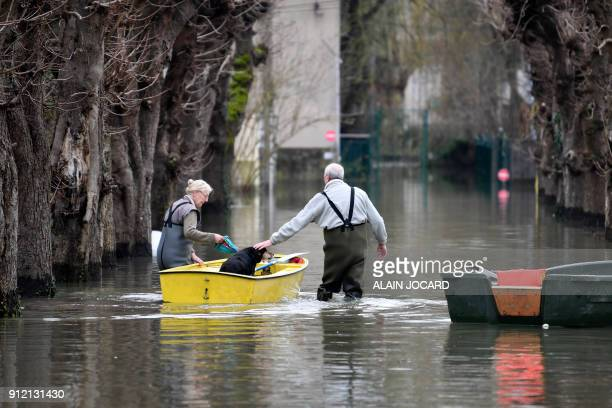 People carry their dog in a rowboat as they walk in a flooded street on January 30 in VilleneuveleRoi near Paris The River Seine peaked on January 29...
